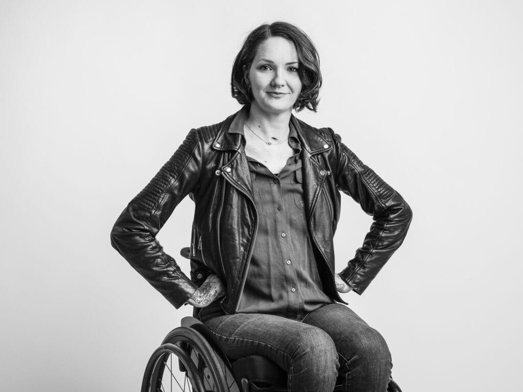 Svartvit porträtt av Yasmin Nilson som tittar mot kameran. Hon sitter i rullstol och håller händerna på höfterna. Hon har på sig skjorta, svart skinnjacka och jeans.