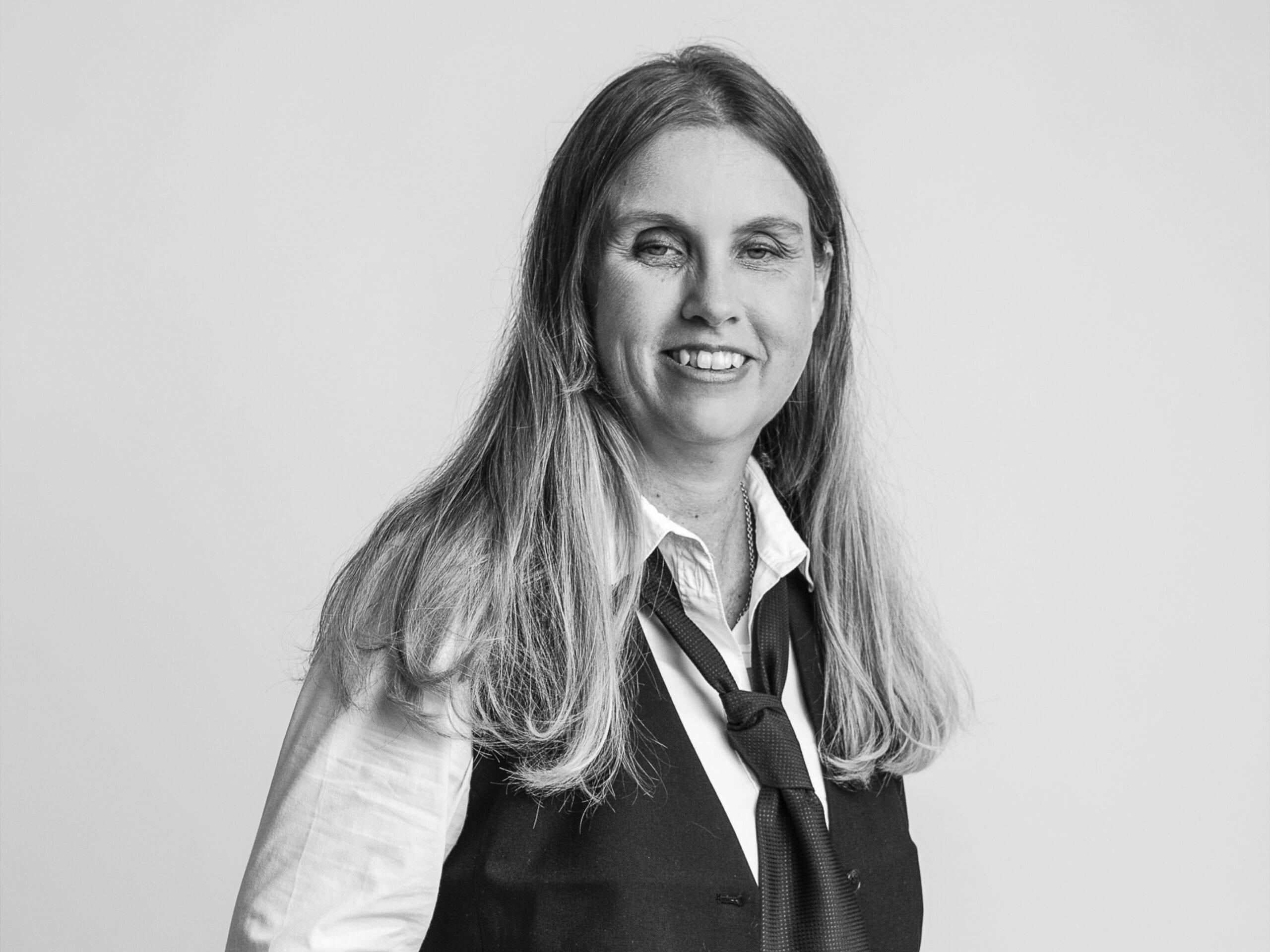 Svartvit porträttbild av Anna Bergholtz. Hon har långt blont hår och ler. Hon har på sig vit skjorta, svart slips och väst.