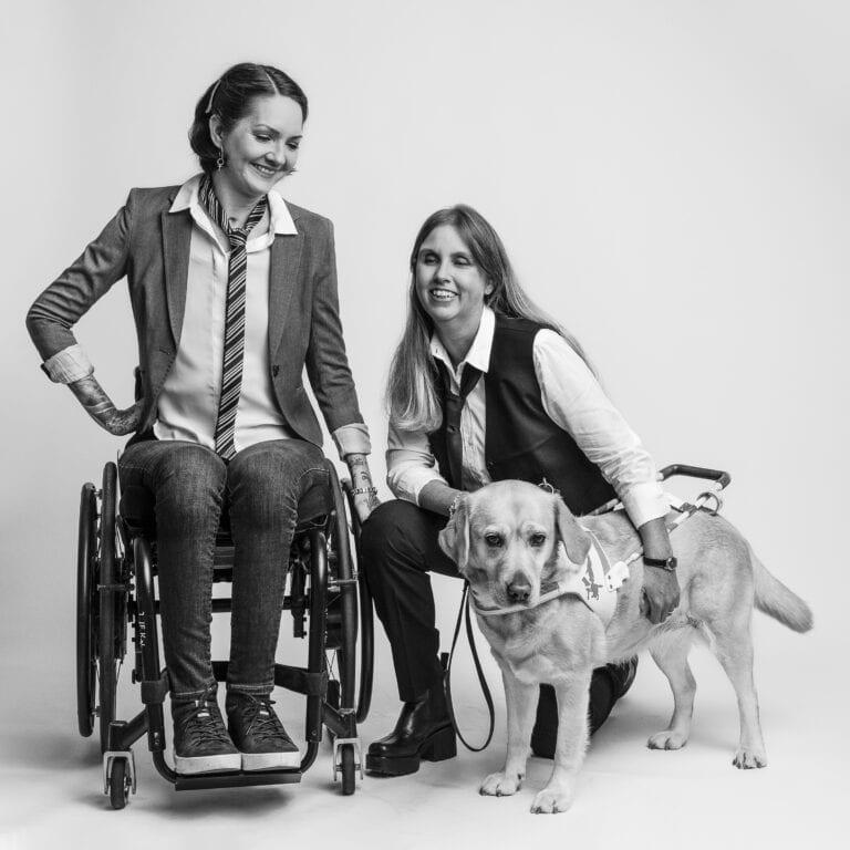 Yasmin Nilson och Anna Bergholtz i fotostudio. Anna står på knä intill sin ledarhund.
