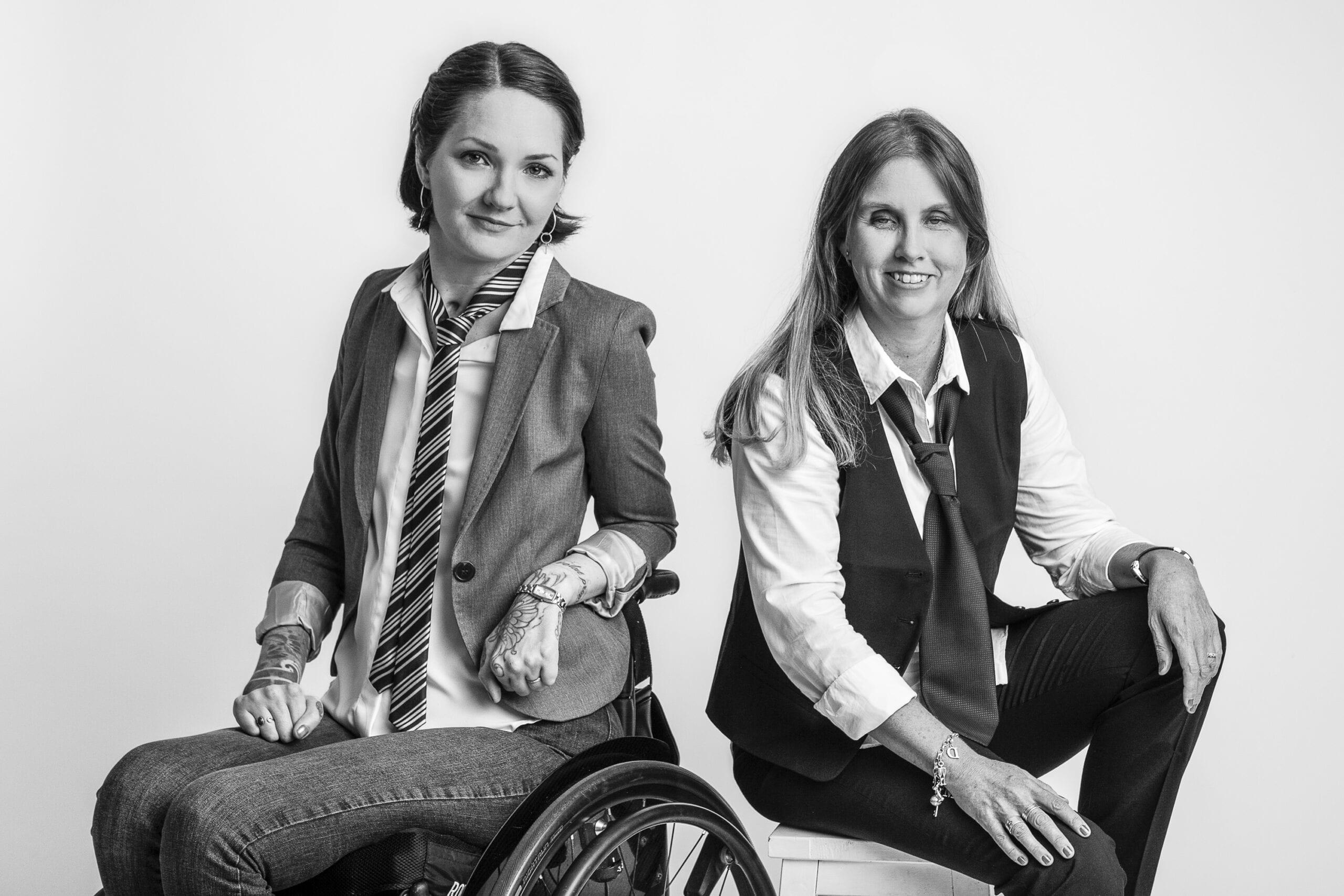 Svartvitt foto på Yasmin Nilson och Anna Bergholtz. De sitter med ryggarna mot varandra, kollar in i kameran och ler. Yasmin sitter i rullstol, har kavaj, randig slips, vit skjorta och jeans. Anna har vit skjorta, svart slips, svart väst och svarta kostymbyxor.