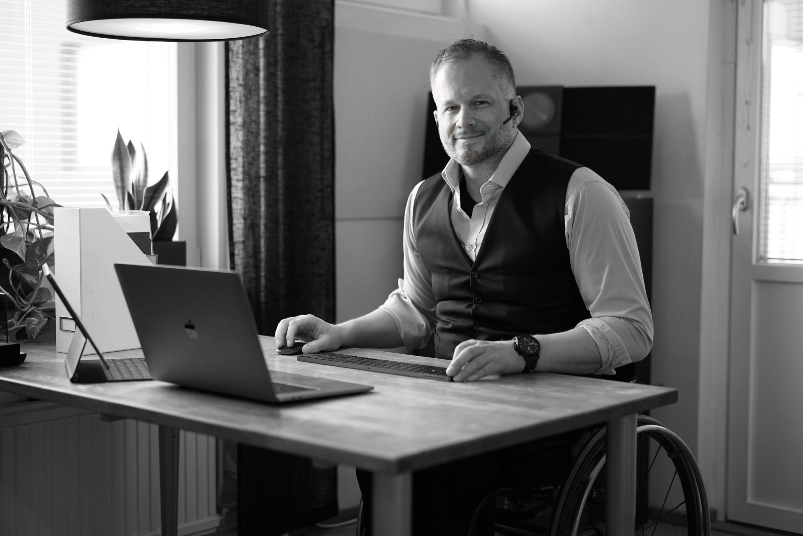 Svartvit bild på en man med vit skjorta och svart väst som sitter i rullstol. Han sitter vid ett skrivbord med headset och laptop.
