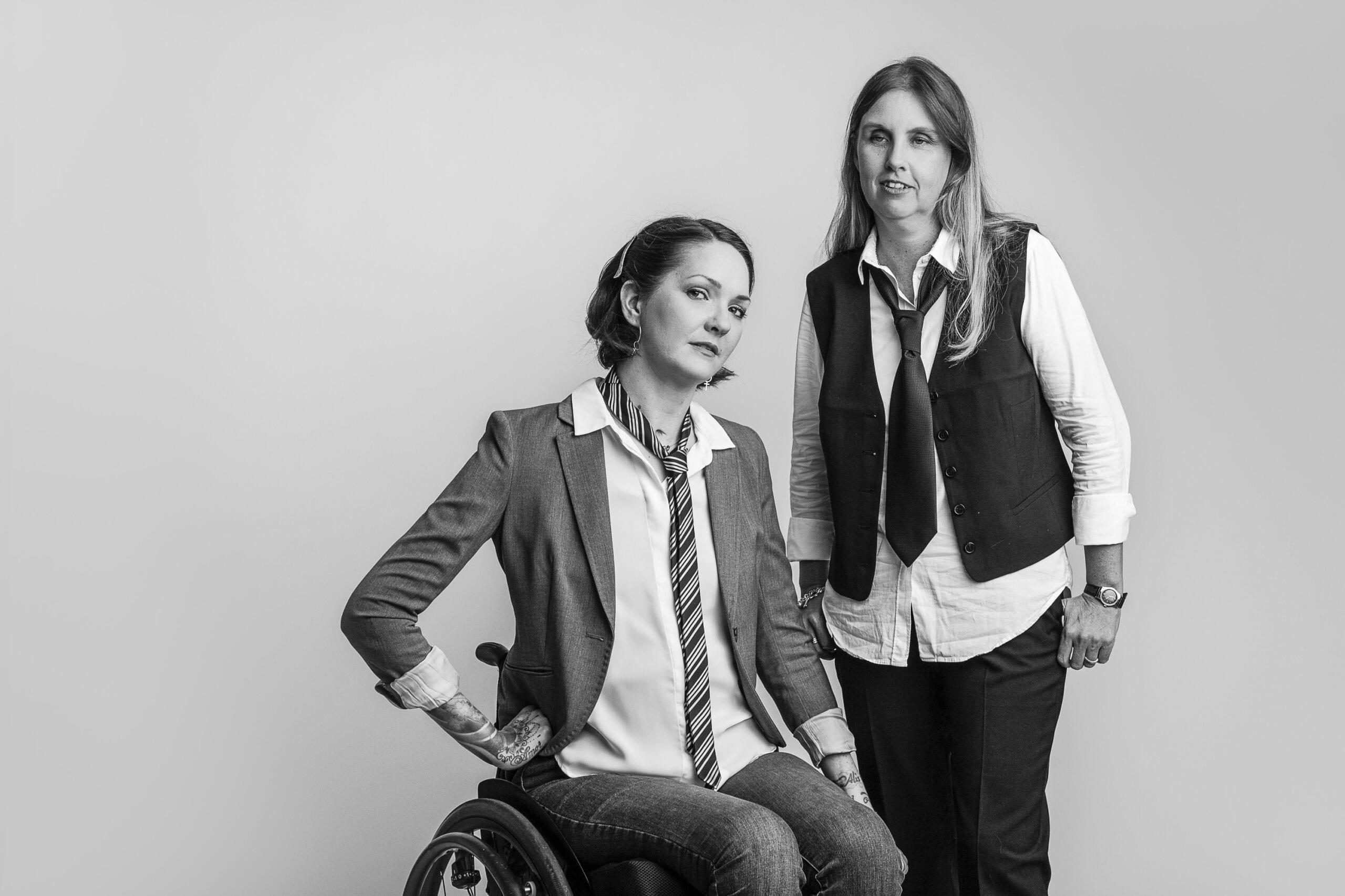 Yasmin och Anna i fotostudio med grå bakgrund. Anna står till höger med självsäker blick. Hon har mörk väst, ljus skjorta, slips och mörka byxor samt långt ljust hår. Yasmin sitter intill i sin rullstol med lutat huvud och tittar mot kameran med självsäker blick iklädd mörk kavaj, slips, ljus skjorta och mörka jeans.