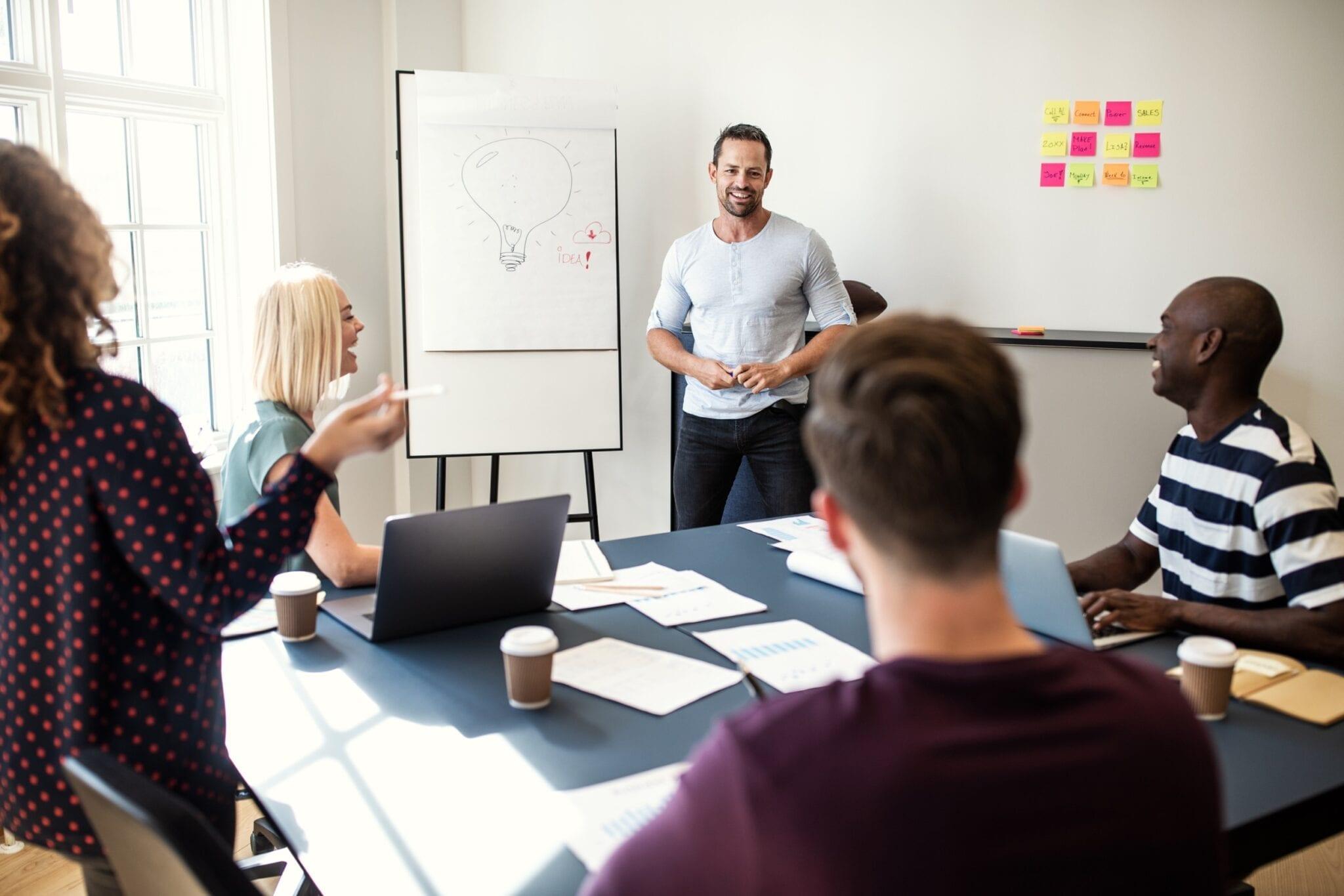 En svartvit bild på en man håller i en presentation för sina medarbetare. Alla skrattar.