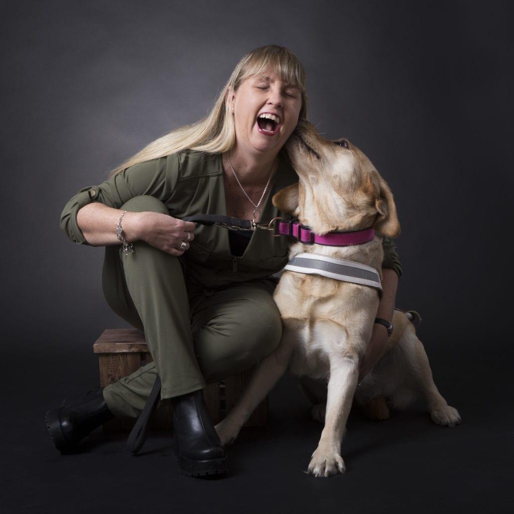 Anna Bergholtz sitter på huk och gapskrattar med sin ledarhund bredvid som slickar henne i örat. Anna har en grön byxdress på sig och långt blont hår. Ledarhunden är en krämfärgad labrador.