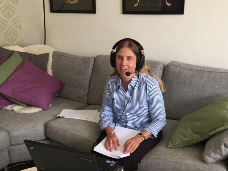 Anna Bergholtz med headset och mick i soffan med datorn framför på soffbordet