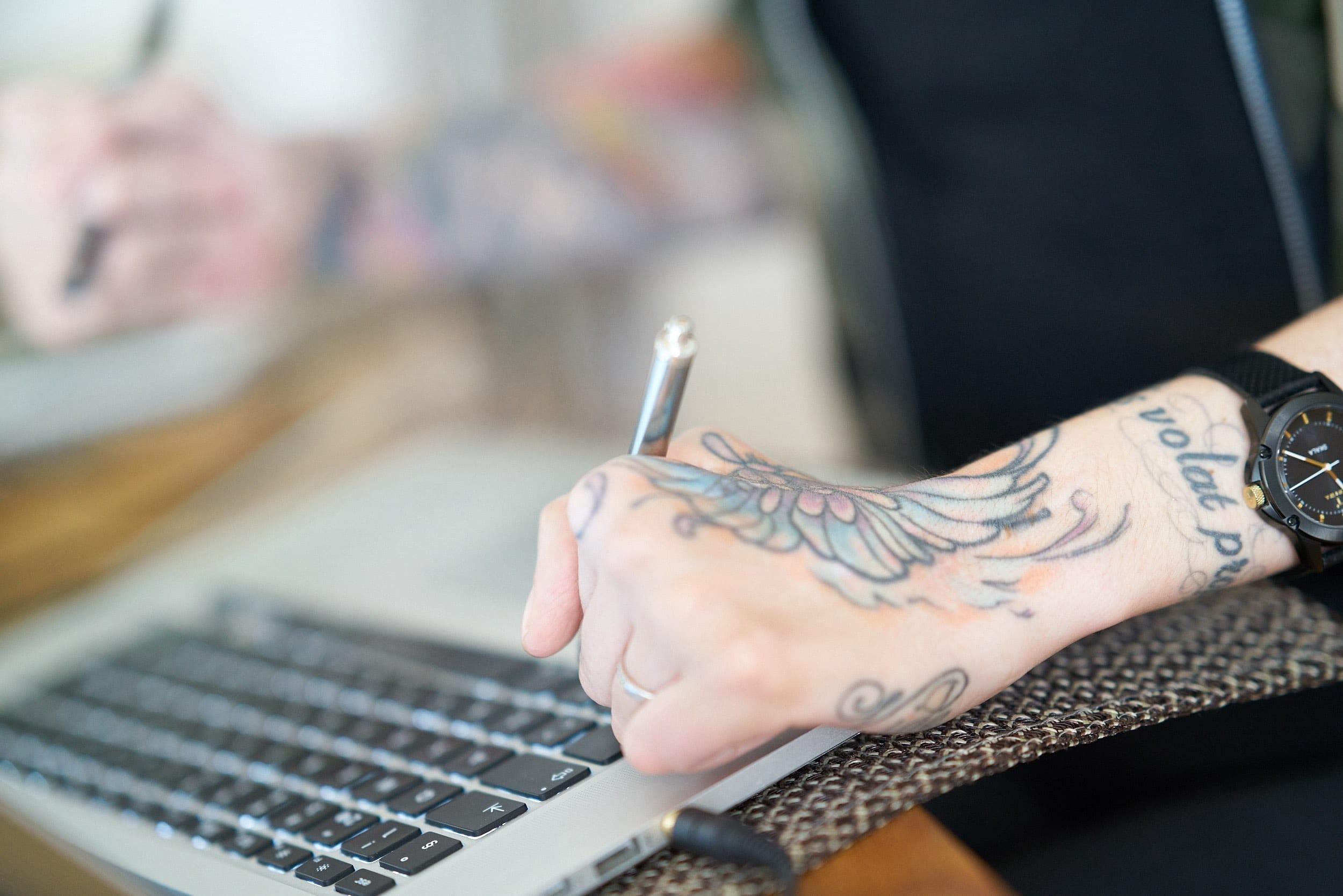Händer med tatuering skriver på datortangentbord
