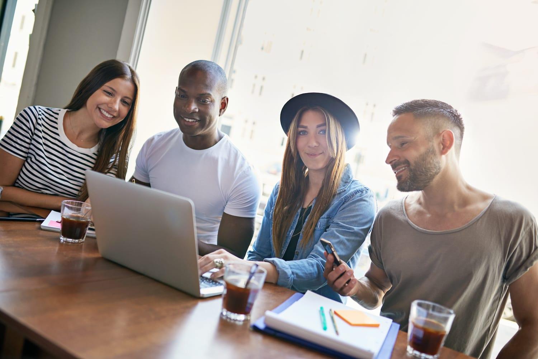 Fyra yngre personer sitter vid bärbar dator och tittar på innehållet