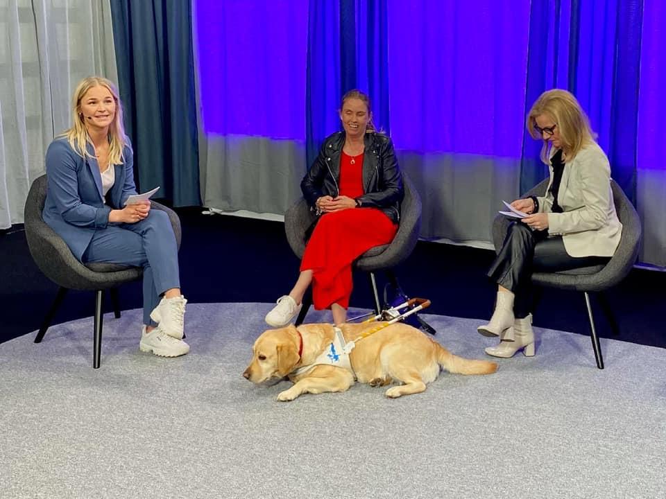 Tre kvinnor sitter bredvid varandra på varsin stol. I mitten ligger en ledarhund i vit sele.