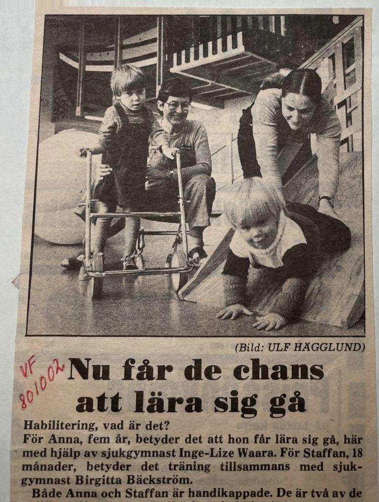 """Foto på ett tidningsurklipp. Staffan och ett annat barn med rullator på barnhabiliteringen. Han är 1,5 år gammal och glider nedför en ramp med armarna före och fysioterapeuten håller i benen. Text: """"Nu får de chans att lära sig gå."""" Foto i reportaget av Ulf Hägglund."""