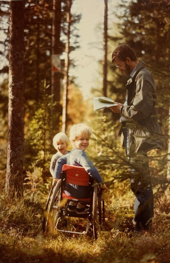 Staffan när han 5 år gammal använder en av sina första rullstolar för barn. Han rullar i skogen med sin far och lillebror. Staffan är vänd mot kameran och ler, lillebror kikar fram skrattande och pappan står och läser i en karta.