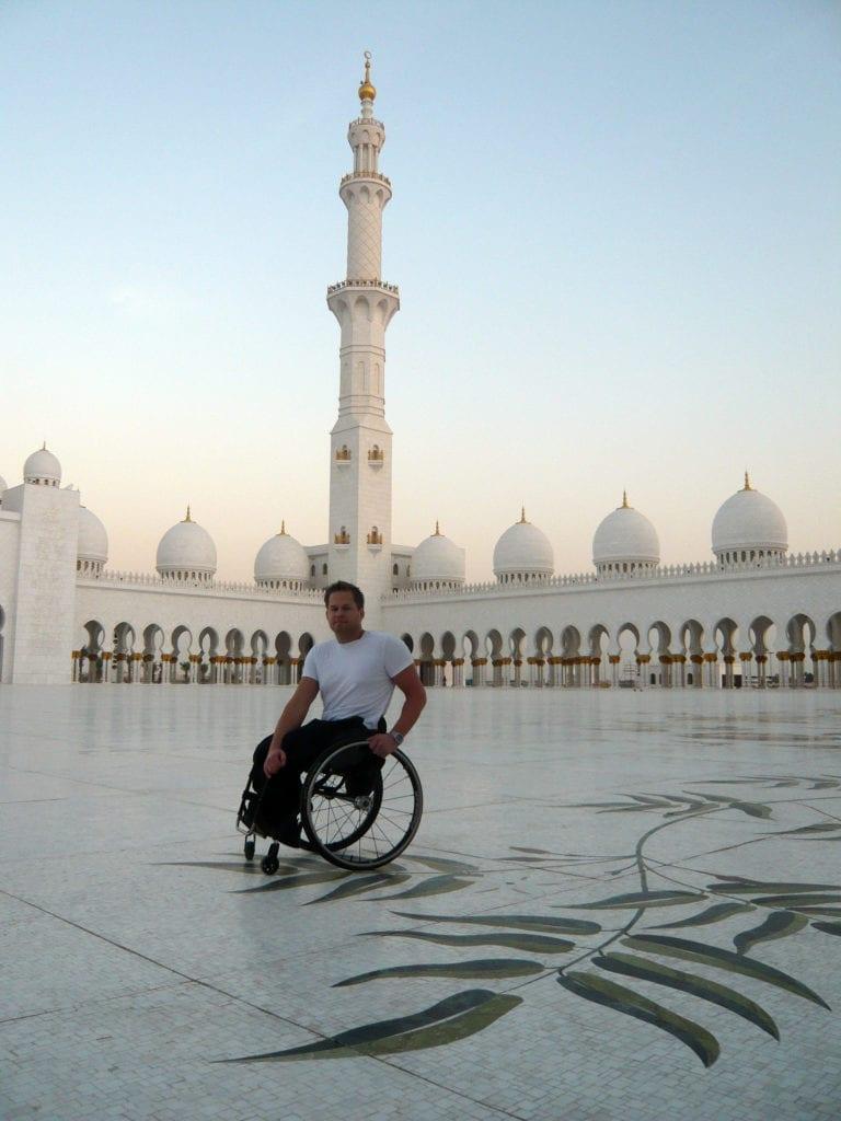 Staffan är på arbetsresa som Rehabinstruktör i Abu Dhabi 2009. Han står på ett vitt mönstrat marmorgolv och orientaliska torn i bakgrunden i Schejk Zayed-moskén. Han har på sig vit T-shirt och svarta byxor.