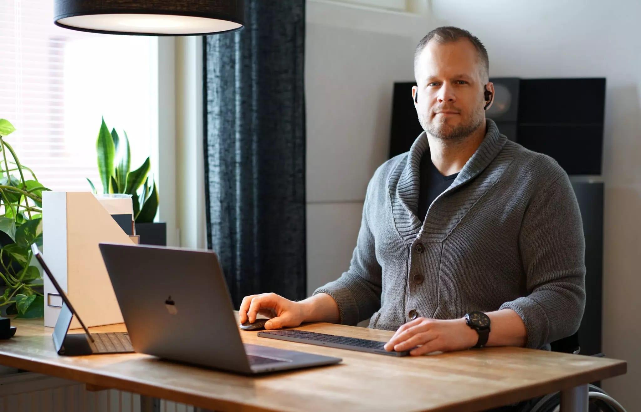 Staffan sitter vid dator med headset. Han har blont kort hår och har på sig en grå cardigan.