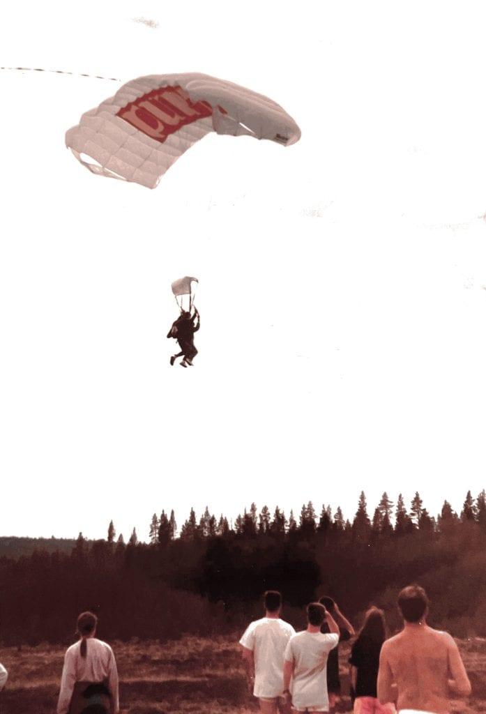 Staffan provar på tandemfallskärmshopp i Västerbotten som tonåring. Staffan seglar ned i fallskärmen och människor står nedanför och tittar.