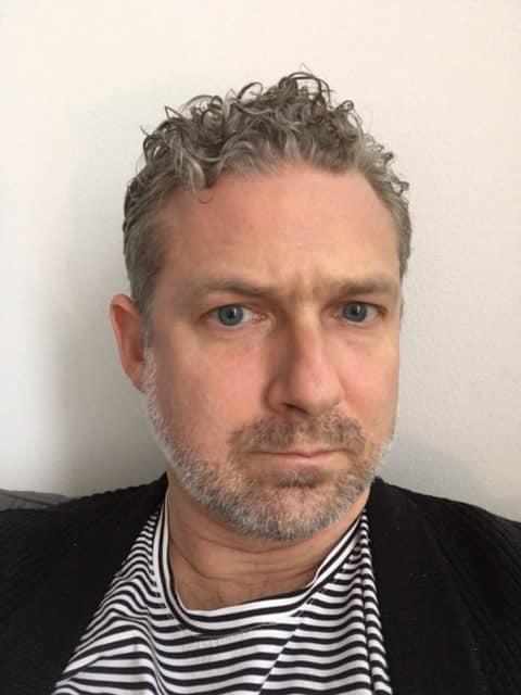 Selfie på Albin som ser allvarlig ut. Han har kort grått lite lockigt hår, grått skäggstubb och blåa ögon. Han har på sig en svart-vit-randig tröja och svart cardigan.