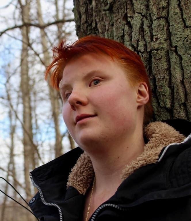 Desideria Jungelin. Hon har kort rött hår, svart jacka med beige pälskrage. I bakgrunden syns träd och blå himmel.