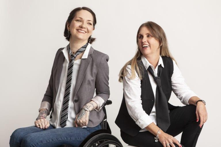 Svartvitt foto på Yasmin Nilson och Anna Bergholtz. De sitter med ryggarna mot varandra, kollar mot varandra och skrattar. Yasmin sitter i rullstol, har kavaj, randig slips, vit skjorta och jeans. Anna har vit skjorta, svart slips, svart väst och svarta kostymbyxor.