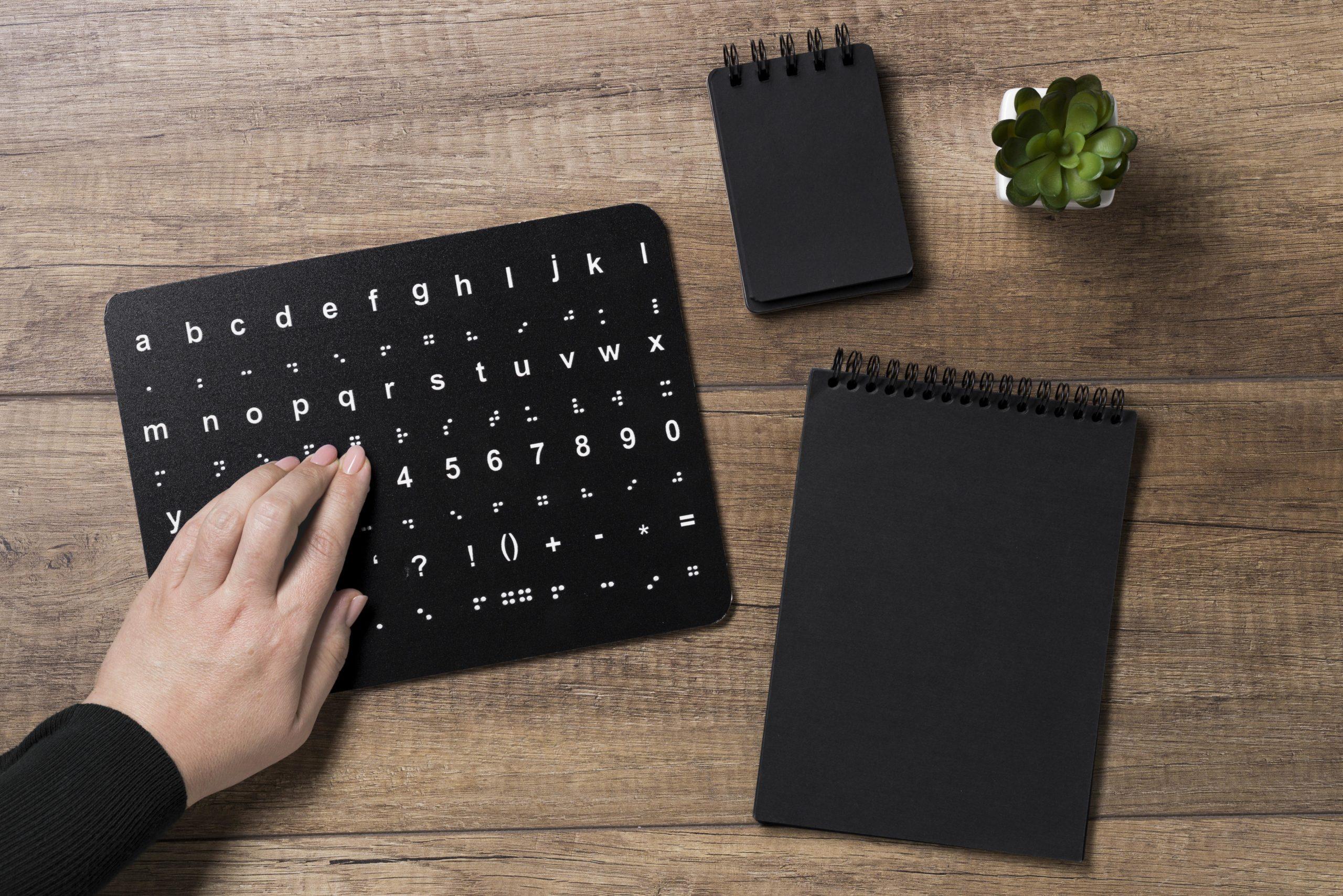 Hand läser punktskrift på en svart tavla.